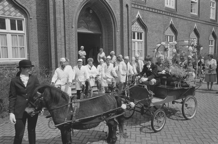In 1985 fotografeerde Thom van Amsterdam een ouder echtpaar in een koets. Mensen in witte doktersjassen staan op de fiets erachter. Wordt hier een jubileum gevierd? Wie kent de mensen op de foto? Waar is dit?