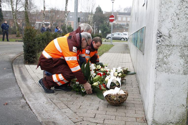 Hulpverleners van het Rode Kruis leggen bloemen neer aan het herdenkingsmonument.