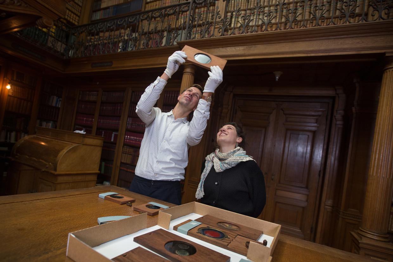 Klaas de Zwaan & Evelien Jonckheere met een glasplaat die geschikt is voor een toverlantaarn.