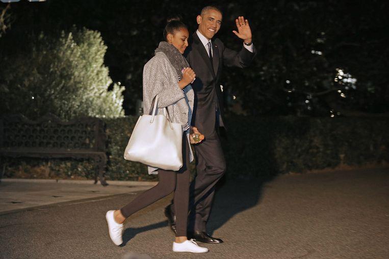 President Barack Obama verlaat samen met dochter Sacha het Witte Huis. Beeld Getty