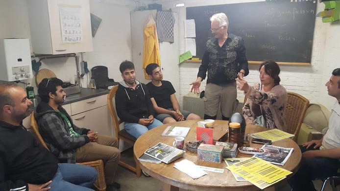Ton Joore (staand) geeft verkeersles aan vluchtelingen uit Syrië, Afghanistan en Iran.