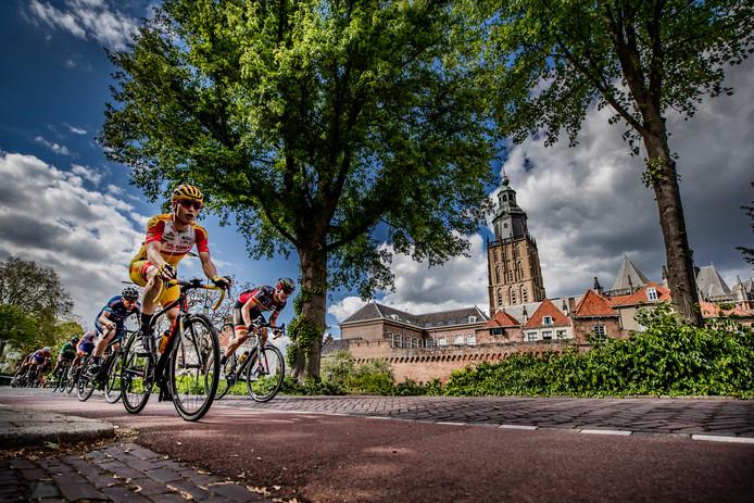 Wielrenners in De Ronde van Zutphen denderen over de Martinetsingel, op de achtergrond de Walburgiskerk.