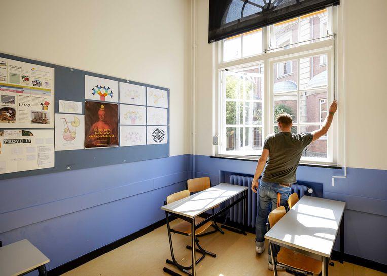 Een leraar van Atheneum College Hageveld zet de ramen open tijdens de voorbereidingen voor het begin van het nieuwe schooljaar.  Beeld ANP