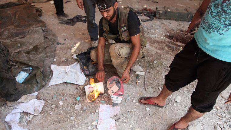 Een Syrische rebel verbrandt een foto van president Assad in Anadan, ten noordwesten van de stad Aleppo. Beeld AFP