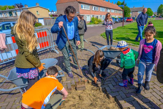 Onder toeziend oog van wethouder Hans Wierikx halen kinderen uit wijk Pagnevaart de eerste klinkers uit de Sparrenstraat ter vergroting van de speelweides.