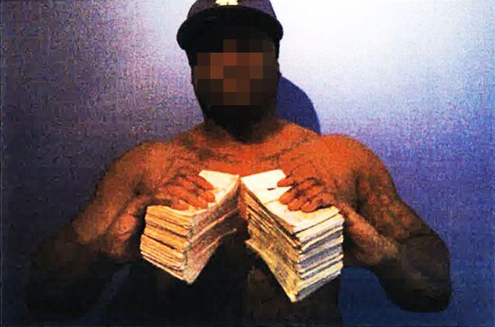 Delano R. poserend met grote stapels geld. Deze foto is opgenomen in het strafdossier van R.