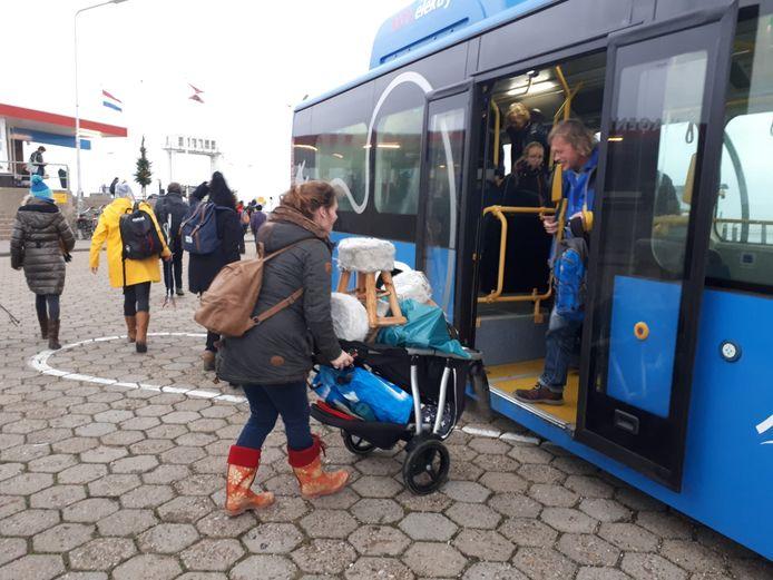 Jean Severijn neemt haar kindje van bijna tweemee naar het vaste land op de arm, de wandelwagen wordt gebruikt om de krukjes te vervoeren.