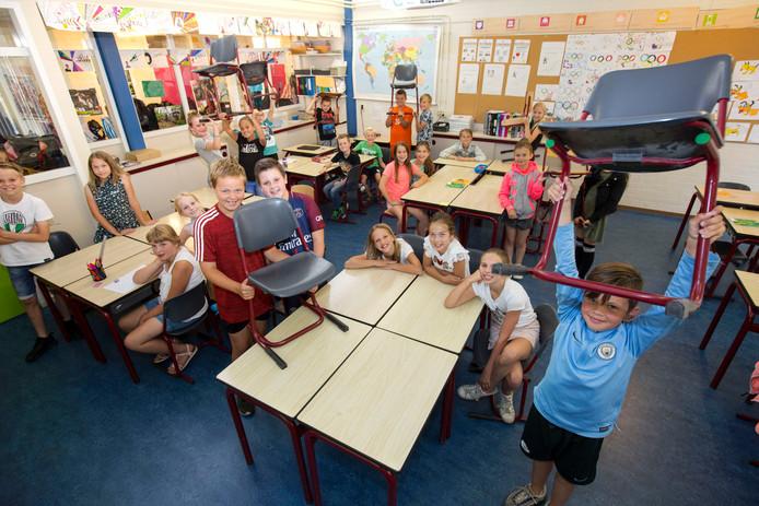 Leerlingen van groep 7 van basisschool De Waterlelie tonen het schoolmeubilair dat naar Gambia wordt verscheept.