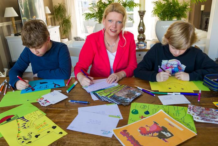 Burgermeester van Heusden Willemijn van Kees schrijft kaarten naar inwoners die een steuntje in de rug kunnen gebruiken. Haar zonen Thomas (L) en Martijn maken tekeningen voor jarigen die  door het coronavirus hun verjaardag niet kunnen vieren.