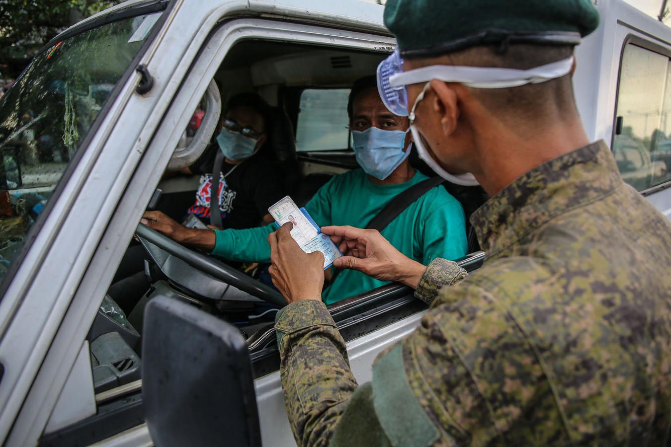 Een corona-controle op de Filipijnen. Alleen met een speciale pas mag je je huis verlaten.