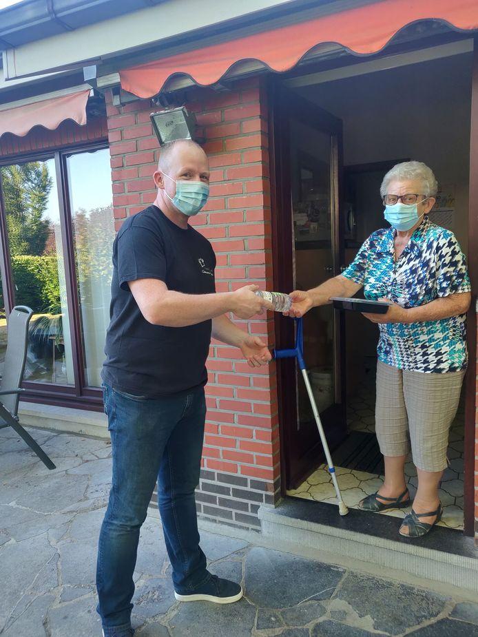 Traiteur André Claessens schenkt een flesje water aan een van zijn klanten.