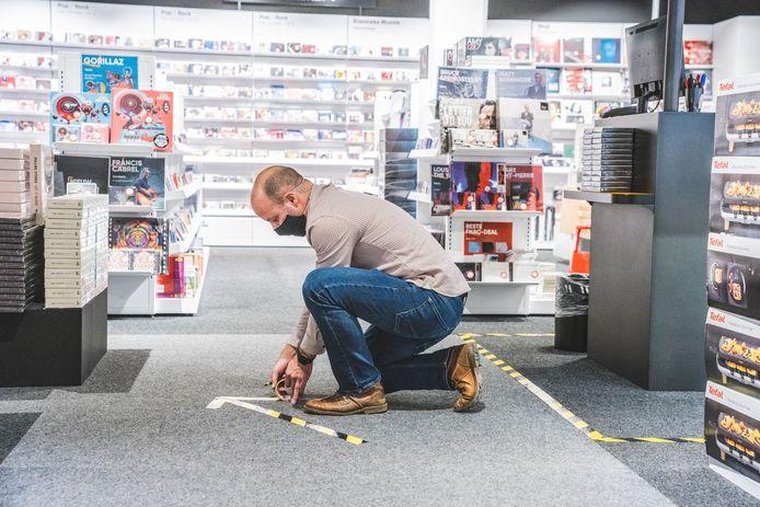 Winkelverantwoordelijke Stijn brengt extra pijlen aan op de grond om de looprichtingen aan te duiden