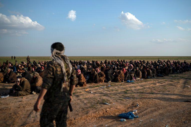 SDF-strijders bewaken mannen die geëvacueerd werden uit het laatste IS-bolwerk in Syrië.