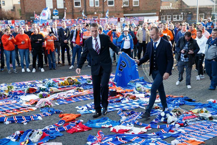 Voorafgaand aan de wedstrijd Rangers - Feyenoord leggen voormalige spelers Gregory Vignal (l) and Thomas Buffel een Rangers-shirt neer voor het stadion, ter ere van hun overleden medespeler Fernando Ricksen. Beeld EPA