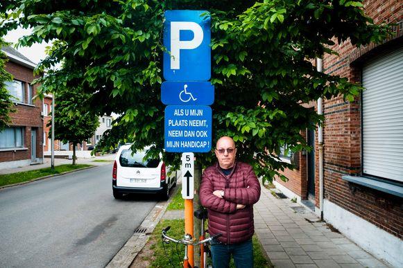 Theo Market bij het verkeersbord voor de parkeerplaats voor gehandicapten.