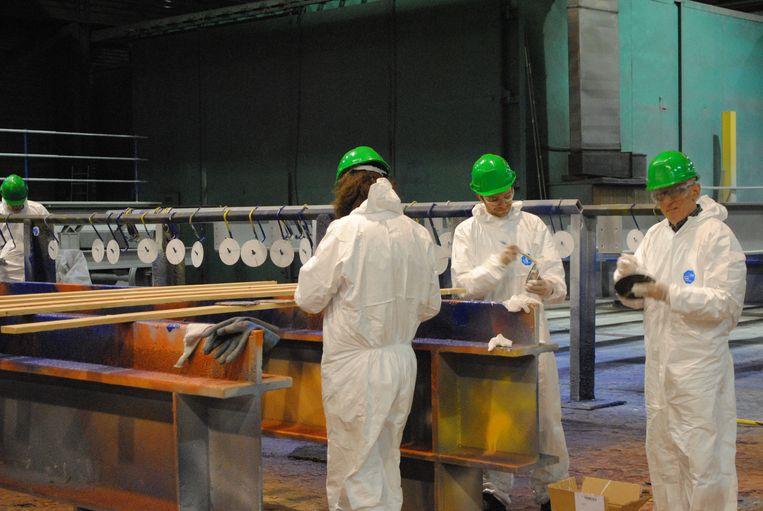 Het KunstBaan-team bereid de slijpschijven voor in de verfhal van Victor Buyck Steel Construction.