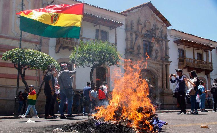Tegenstanders van president Evo Morales stichten brand op straat en houden de Boliviaanse vlag omhoog in Sucre.