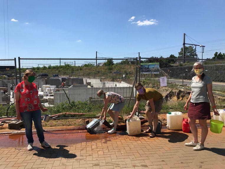 Emmertjes water halen als protest tegen de verspilling van grondwater op bouwwerven. Van links naar rechts: Betty Kiesekoms, Nele Weckhuyzen, Thomas Salaets en Petra Vanlommel van Groen Aarschot