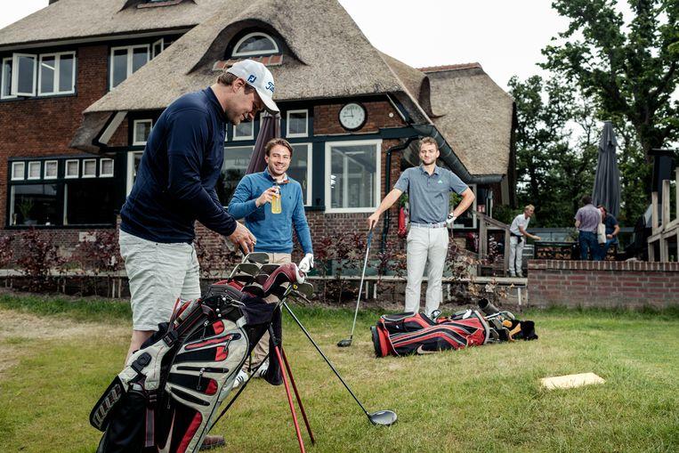 Golfers met op de achtergrond het historische clubhuis van de Amsterdam Old Course.  Beeld Jakob Van Vliet