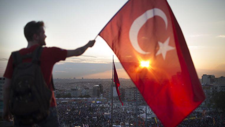 Een demonstrant met de Turkse vlag op het Taksimplein. Beeld getty