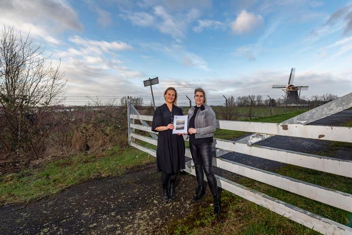 Annelies van Loenhout van de dorpsraad overhandigt het plan, met daarin de visie van de dorpsraad voor het gebied rondom bungalowpark Sunclass, aan wethouder Esther Prent (l) bij het oude zwembad.