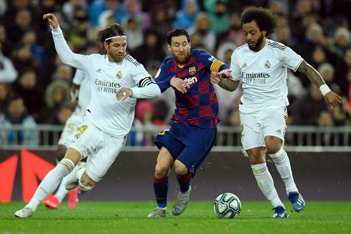 Lionel Messi op archiefbeeld in duel met Real-spelers Sergio Ramos (l) en Marcelo.