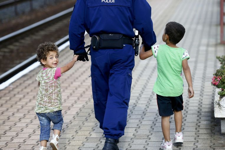 Een politieman begeleidt twee vluchtelingenkinderen op het station in Hegyeshalom, waar de trein naar München vertrekt. Beeld reuters