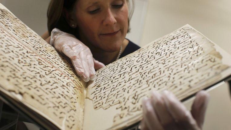 Conservator Marie Sviergula houdt het pas ontdekte stuk Koran vast in de bibliotheek van de Universiteit van Birmingham. Beeld reuters