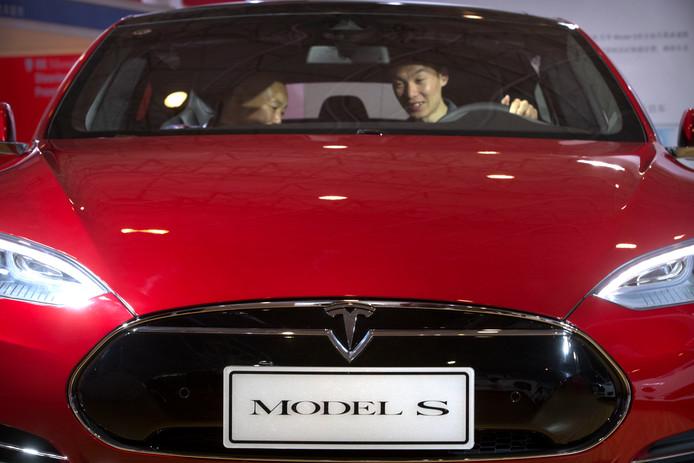 Een man zit in een Tesla (van Amerikaanse makelij) op de International Automotive Exhibition in Peking.