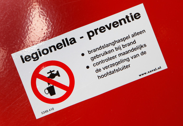 Een sticker van legionellapreventie op een brandslangkast in een kantorenpand.
