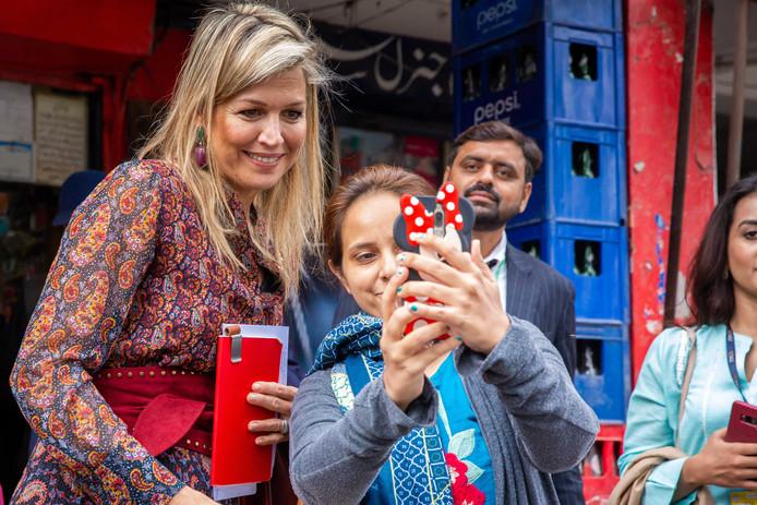 Koningin Máxima gaat op de foto na een bezoek aan de eigenaar van een supermarkt op de Ghalib Markt in Lahore gisteren.