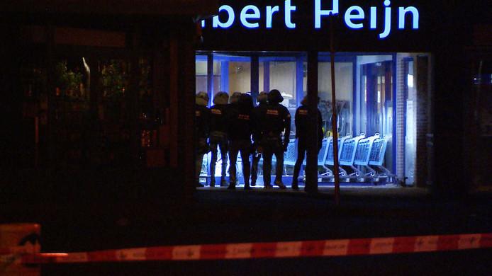Een arrestatieteam van de politie bij een filiaal van Albert Heijn in 's-Gravendeel na de plofkraak vanmorgen bij de supermarkt.