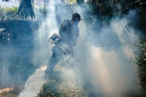 Een arbeider verspreidt pesticiden tegen de muggen in Bangkok, Thailand.