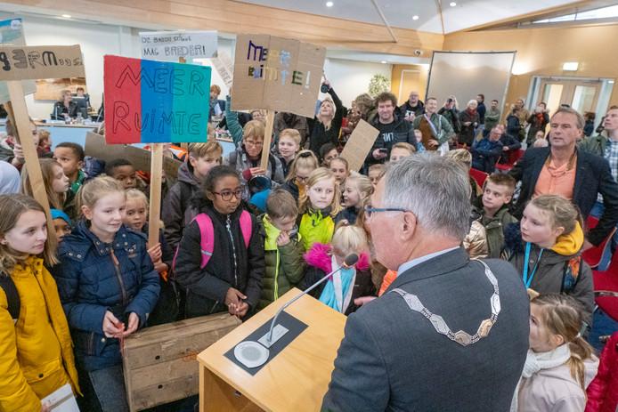 Burgeneester Gerard Rabelink neemt in de raadszaal de handtekeningen in ontvangst voor snelle uitbreiding van de Theo Thijssenschool in Zierikzee.