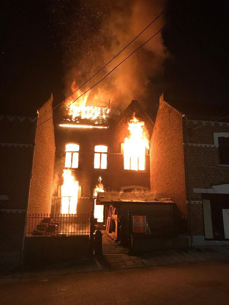 De vlammen slaan door het dak en de ramen van de woning.
