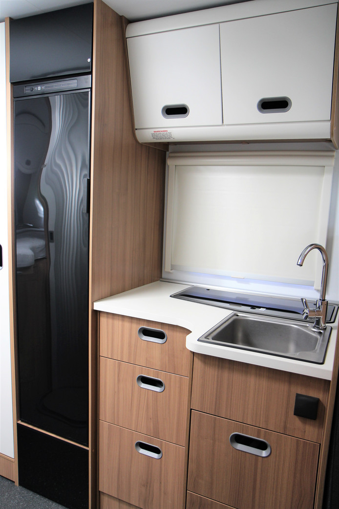 De keuken met links de grote koelkast en ook hier weer veel handige kastruimte en laden. Een afzuigkap ontbreekt, maar het raam achter de kookplaat kan worden open gezet
