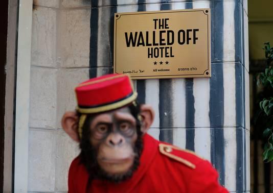 Voor de ingang staat een beeld van een aap verkleed als bellboy