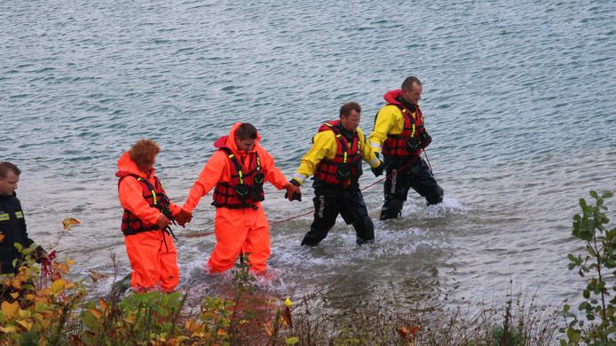 Duikers en oppervlakteredders van de brandweer zoeken in de plas naar een mogelijke drenkeling.