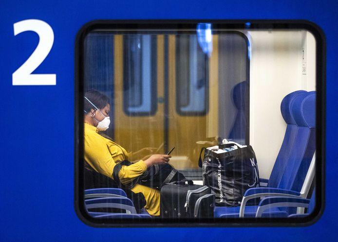 Een reiziger met een mondkapje op station Den Haag Centraal. De NS heeft opgeroepen om niet met de trein te reizen als dit niet strikt noodzakelijk is om zo de verspreiding van het coronavirus tegen te gaan.