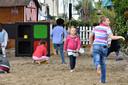 ... terwijl de kinderen zich uitleven in het zand.