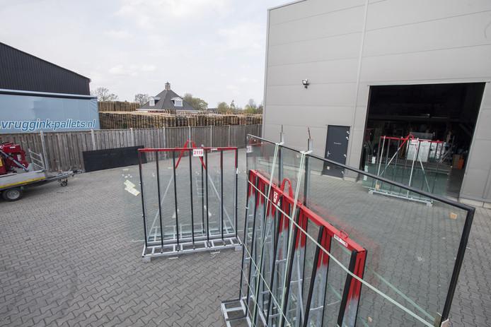 Vruggink heeft de stapels pallets op last van de gemeente Wierden verlaagd, maar ze staan nog steeds dicht op het pand van de Twentse Glasgroep (rechts).