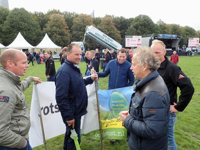 Oud-staatssecretaris van landbouw Henk Bleker (CDA, rechts) bekijkt het spandoek dat Zeeuws-Vlaamse boeren hebben meegenomen. Bleker was afgelopen dinsdag een van de sprekers tijdens de demonstratie op het Haagse Malieveld.
