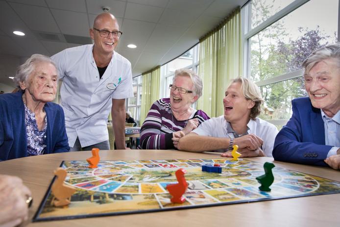 Frank Schenk (links, wit jasje) en Gijs Groeneveld doen een spelletje ganzenborden met verpleeghuisbewoners.