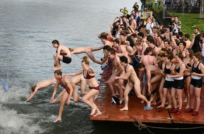 Traditiegetrouw duiken de studenten na afloop van de roeiwedstrijd schaars gekleed het kanaal in.