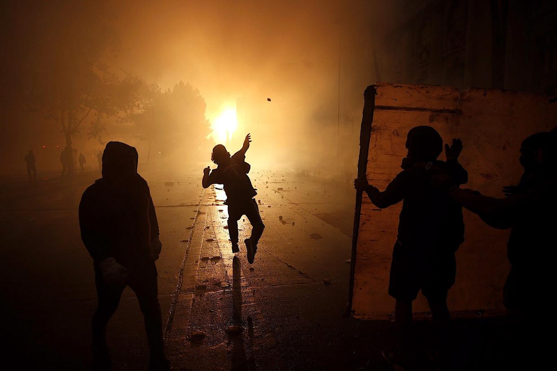 Demonstranten in de straten van Santiago.  Beeld EPA