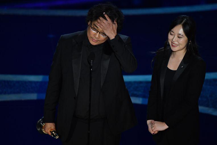 De totaal verbouwereerde Zuid-Koreaanse regisseur Bong Joon-ho met de Oscar voor beste regisseur. Met zijn film Parasite won Bong maar liefst vier prijzen. Beeld AFP