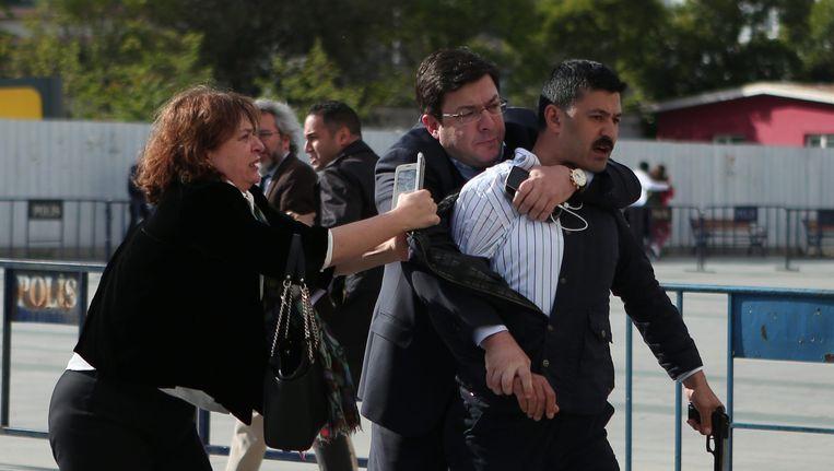 Dündars echtgenote en een oppositieparlementslid proberen de schutter, met zijn wapen nog in de hand, te overmeesteren.
