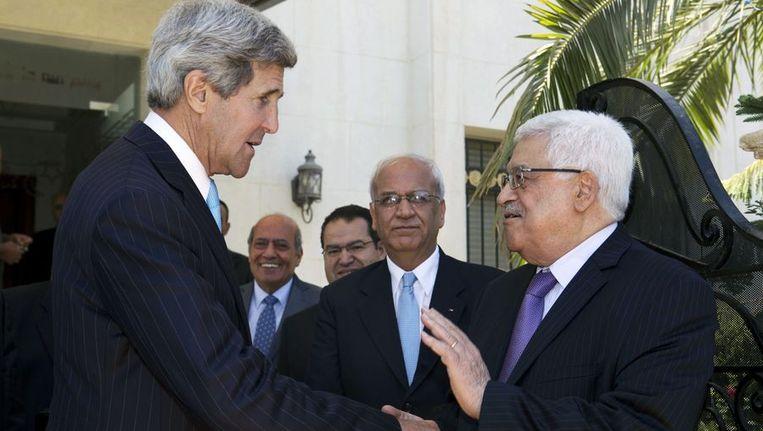 John Kerry schudt de hand van de Palestijnse president Mahmoud Abbas. Beeld afp