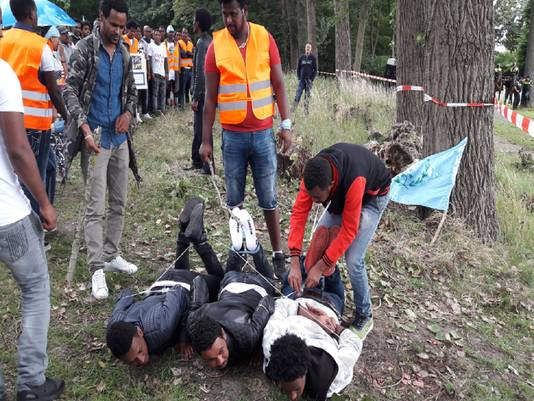 Demonstranten uit Eritrea spelen in Rijswijk na hoe het regime in het Afrikaanse land met gevangenen omgaan. Met een stok wordt gedaan alsof de geknevelde mannen op de grond worden geslagen.