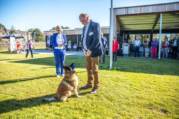 Hond Roxy levert de sleutel van het nieuwe gebouw van de Kynologenclub Zwolle en Meppel keurig af bij haar baasje.